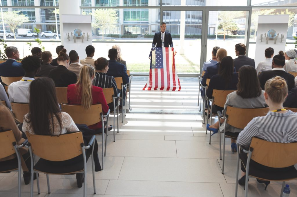 Mixed race man speaker speaking in a business seminar in office building with american flag